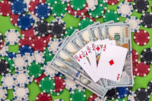 Fichas de póquer con cartas y dólares sobre la mesa.