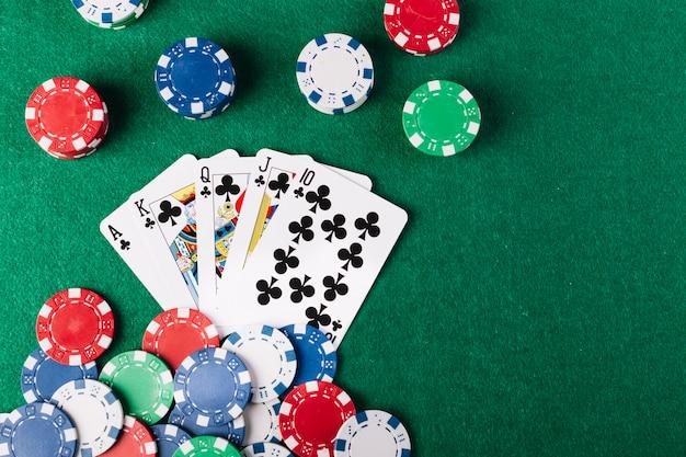 Fichas de póquer y club de la escalera real en la mesa de póquer verde