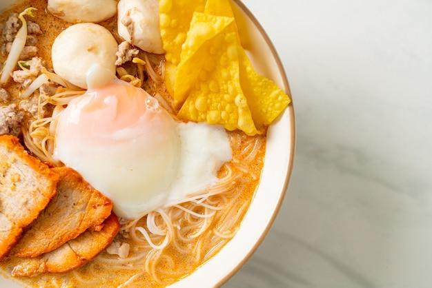 Fideos de arroz con albóndigas, cerdo asado y huevo en sopa picante - tom yum noodles
