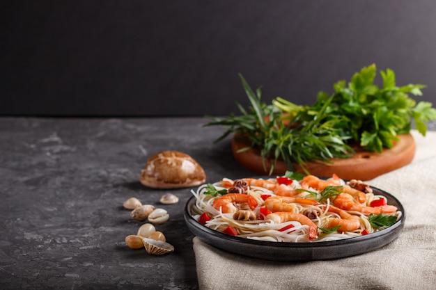 Fideos de arroz con camarones o langostinos y pequeños pulpos en placa de cerámica gris sobre hormigón negro. vista lateral, copyspace.