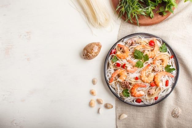 Fideos de arroz con camarones o langostinos y pequeños pulpos en placa de cerámica gris sobre una madera blanca. vista superior.