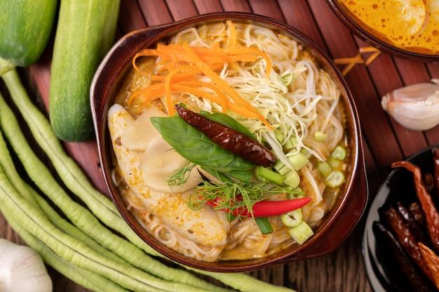 Fideos de arroz, curry rojo con albóndigas, con chiles secos, albahaca, pepino y habichuelas