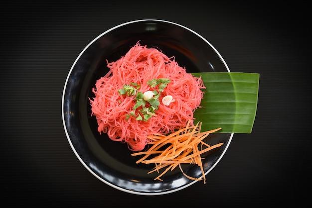 Fideos de arroz, frituras rosadas y vegetales fideos de arroz salteados con salsa roja servidos