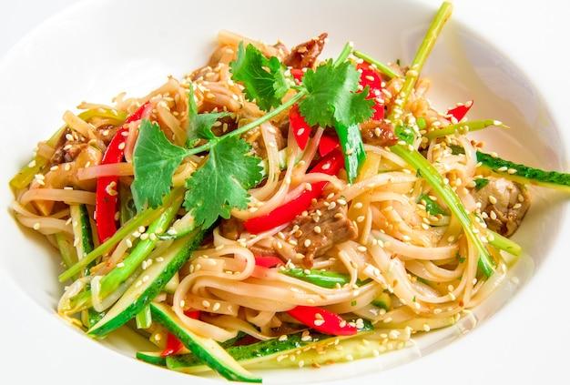Fideos de arroz panasiáticos con carne de res, verduras, brotes de soja en salsa agridulce