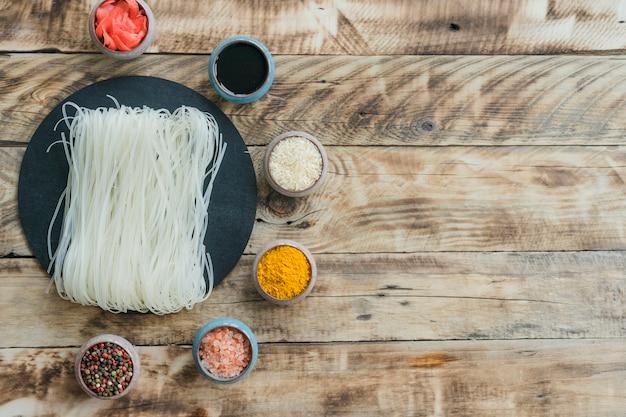 Fideos de arroz en roca de pizarra redonda rodeada de granos de pimienta; cúrcuma; arroz; salsa y jengibre en escabeche