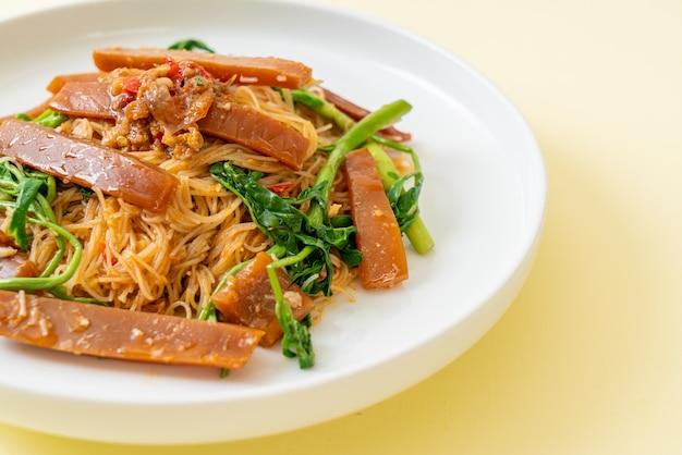 Fideos de arroz salteados y mimosa de agua con calamares en escabeche - comida asiática