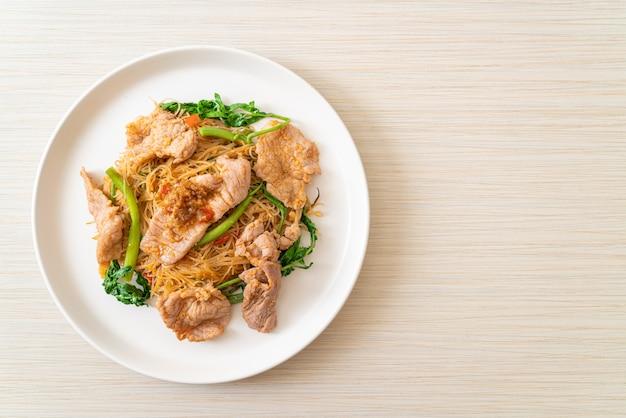 Fideos de arroz salteados y mimosa de agua con cerdo - estilo asiático