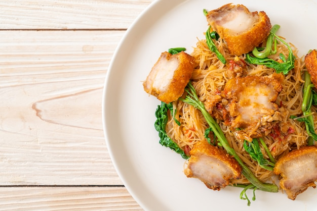 Fideos de arroz salteados y mimosa de agua con crujiente panceta de cerdo - estilo de comida asiática