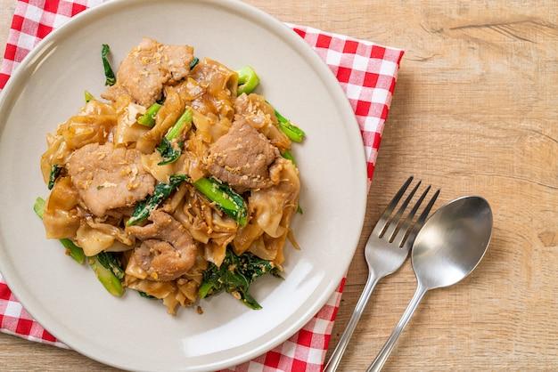 Fideos de arroz salteados con salsa de soja negra y cerdo y col rizada - estilo de comida asiática