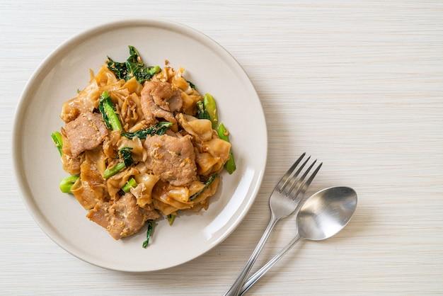 Fideos de arroz salteados con salsa de soja negra y cerdo y col rizada