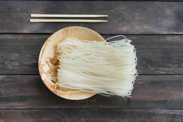 Fideos de arroz seco en placa con palillos sobre tabla de madera