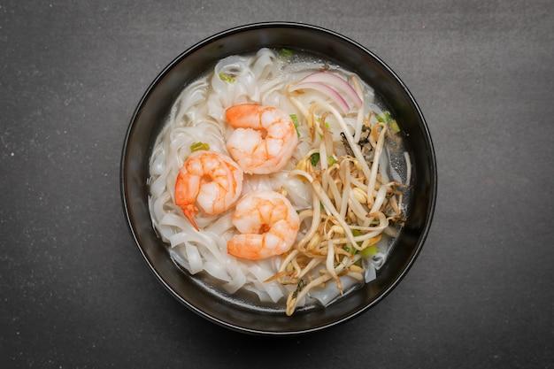 Fideos asiáticos con camarones y mariscos en un tazón negro