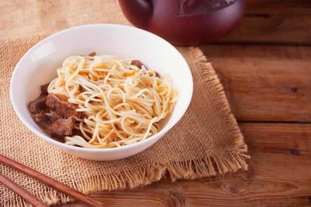 Fideos asiáticos con carne de res, verduras en un tazón con palillos, de madera rústica. cena de estilo asiático. fideos chinos japoneses