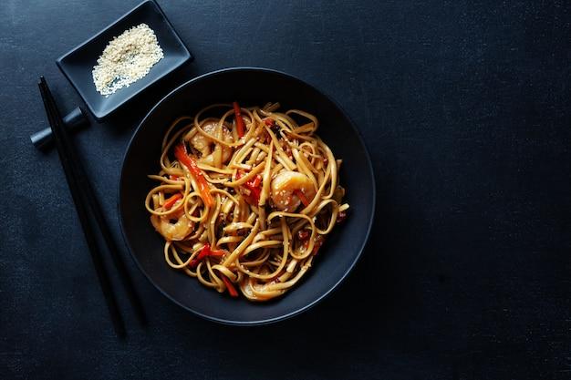 Fideos asiáticos con gambas y verduras servidos en un recipiente sobre fondo oscuro.