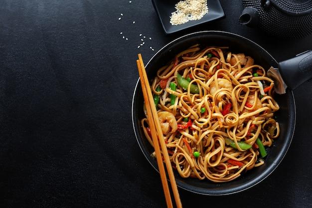 Fideos asiáticos con gambas y verduras servidos en sartén sobre fondo oscuro.
