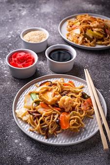 Fideos asiáticos con gambas y verduras.