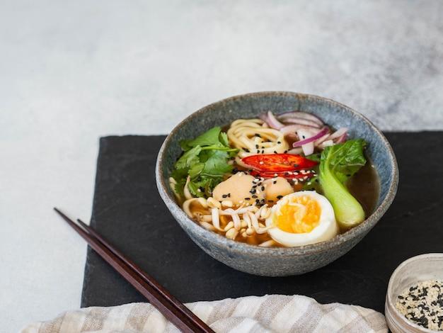 Fideos asiáticos de ramen con pollo, repollo pak choi y huevo
