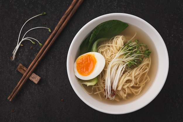 Fideos asiáticos de sopa (ramen) con huevo sobre fondo oscuro