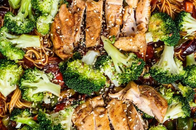 Fideos asiáticos con verduras y carne en la sartén. vista superior