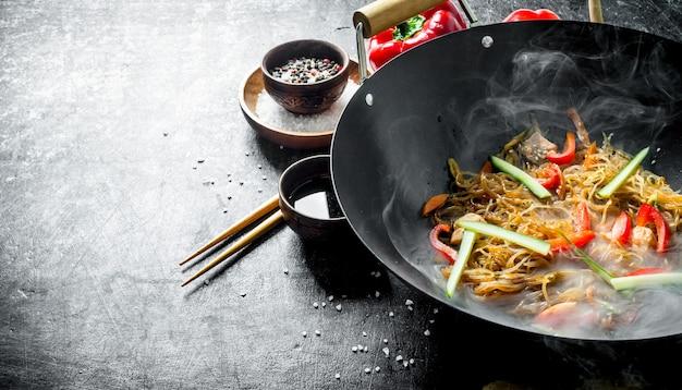 Fideos calientes de celofán en una sartén wok con pimientos, pepino y zanahoria. en rústico oscuro