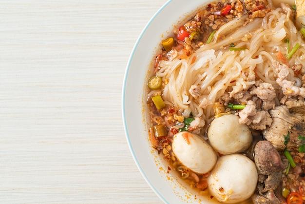 Fideos con carne de cerdo y albóndigas en sopa picante o fideos tom yum al estilo asiático