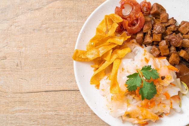 Fideos chinos de arroz al vapor con cerdo y tofu en salsa de soja dulce, estilo comida asiática