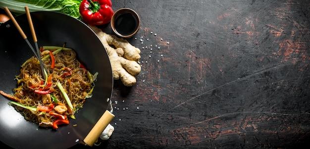 Fideos chinos recién cocinados wok funchoza con salmón, verduras y salsa en la mesa de madera oscura.