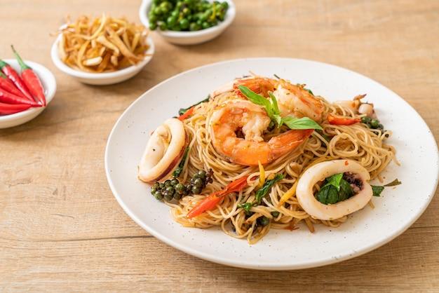 Fideos chinos salteados con albahaca, guindilla, camarones y calamares - estilo de comida asiática
