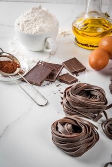 Fideos crudos de pasta de chocolate sin preparar, con ingredientes para cocinar: chocolate, cacao, harina, huevos, aceite. sobre una mesa de mármol blanco de cocina. copyspace