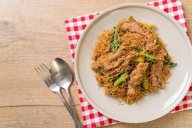 Fideos fideos de arroz salteados con salsa de soja negra y cerdo - estilo de comida asiática