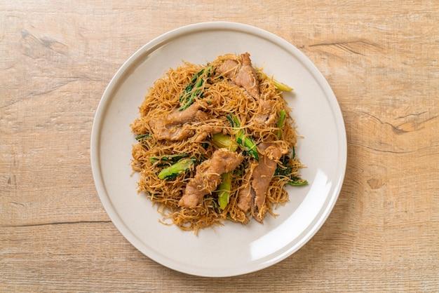 Fideos de fideos de arroz salteados con salsa de soja negra y cerdo - estilo de comida asiática