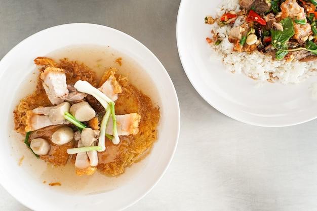 Fideos de fideos fritos con topping de cerdo crujiente en salsa gravy en la placa blanca.