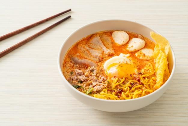Fideos de huevo con carne de cerdo y albóndigas en sopa picante o tom yum noodles al estilo asiático