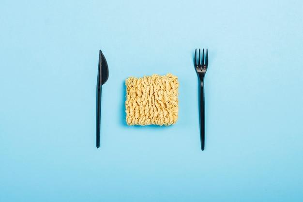 Fideos instantáneos asiáticos y platos desechables de plástico sobre una superficie azul. el concepto de comida rápida, comida rápida, comida chatarra. vista plana, vista superior.