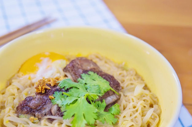 Fideos instantáneos con carne de cerdo y huevo listos para comer: concepto de menú de comida instantánea deliciosa