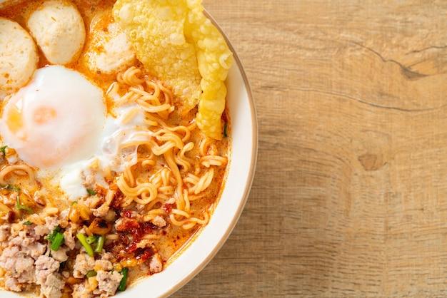 Fideos instantáneos con cerdo y albóndigas en sopa picante o tom yum noodles al estilo asiático