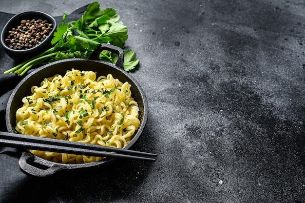 Fideos instantáneos cocidos con carne de soja en una olla. plato vegetariano. fondo negro. vista superior. copie el espacio.
