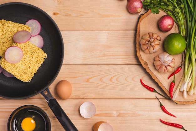 Fideos instantáneos para cocinar y comer en el plato con huevos y verduras sobre fondo de madera.