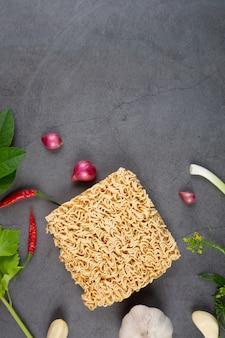 Fideos instantáneos crudos listos para cocinar aislar con ingrediente de sopa agridulce en la pared negra.