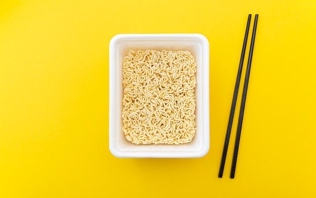 Fideos instantáneos en un paquete blanco como comida asiática tradicional y palillos sobre fondo amarillo, composición de alimentos, endecha plana, vista superior