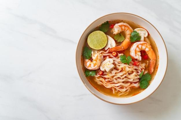 Fideos instantáneos ramen en sopa picante con camarones (tom yum kung) - estilo de comida asiática