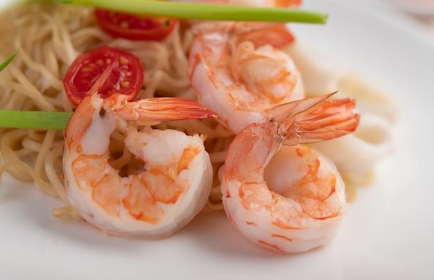Fideos instantáneos salteados con langostinos y palitos de cangrejo en un plato blanco.