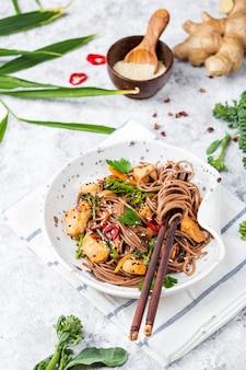 Fideos japoneses de alforfón yakisoba con pollo y verduras sobre un fondo claro