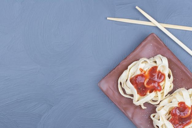 Fideos de pasta con salsa de ají dulce en bandeja de madera.