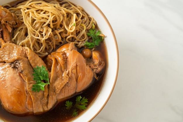 Fideos con pollo estofado en un tazón de sopa marrón - estilo de comida asiática