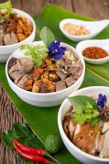 Fideos de pollo en un tazón con guarniciones, comida tailandesa