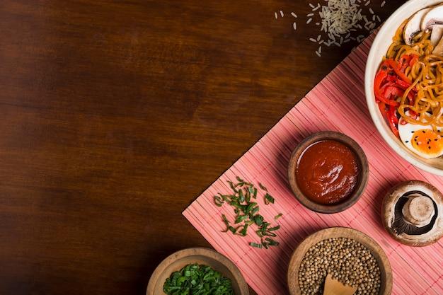 Fideos ramen al estilo asiático con salsas; cebollino y semillas de cilantro sobre mantel sobre la mesa de madera