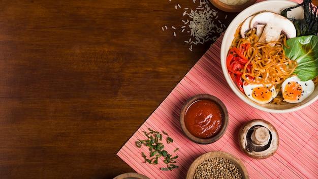 Fideos ramen en estilo asiático con salsas en mesa de madera