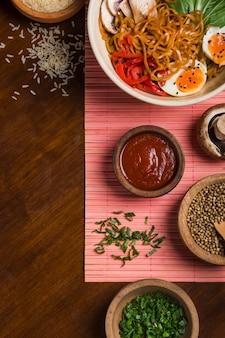 Fideos ramen con huevo; ensalada; cebollino semillas de cilantro; grano de arroz y salsa en mesa de madera