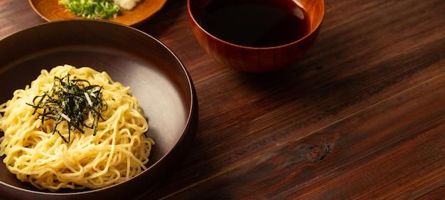 Fideos ramen japoneses fríos con cebollas verdes picadas, wasabi rallado y una taza para salsa